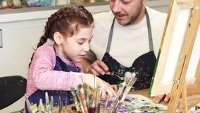 Tir cultivé de parler de sourire mignon de petite fille à ses peintures de mélange de papa à la classe d'art banque de vidéos