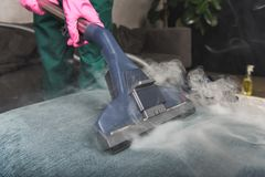 tir cultivé de sofa de nettoyage de personne avec la vapeur chaude d'aspirateur photos libres de droits