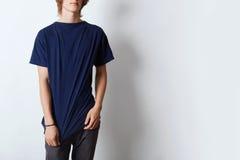 Tir cultivé de T-shirt de port de type beau de hippie avec l'espace vide pour votre publicité ou texte Jeune pose masculine contr Photo libre de droits