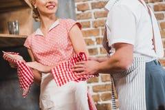 tir cultivé des couples dans les tabliers lavant et séchant des plats ensemble photos libres de droits