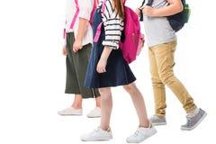 tir cultivé des enfants avec des sacs à dos marchant ensemble d'isolement sur le blanc Images stock