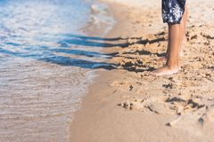 tir cultivé des enfants se tenant sur la plage sablonneuse Photos stock