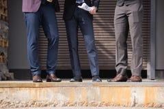Tir cultivé des hommes d'affaires élégants dans le formalwear se réunissant dehors à la coupure Photo stock