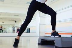 Tir cultivé des jambes maigres de femme faisant l'aérobic d'étape Image libre de droits
