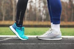 Tir cultivé des jambes masculines et femelles dans des chaussures de course près de Photo libre de droits