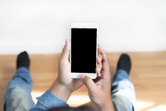 Tir cultivé des mains de l'homme tenant le téléphone intelligent avec la copie vide Images stock