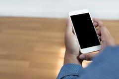 Tir cultivé des mains de l'homme tenant le téléphone intelligent avec la copie vide Photographie stock libre de droits
