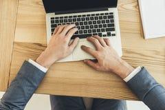 Tir cultivé des mains masculines dactylographiant sur un ordinateur portable placé photographie stock