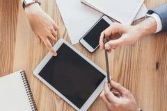 Tir cultivé des mains masculines jugeant un crayon et une main femelle se dirigeant sur un écran numérique de comprimé plus de image stock