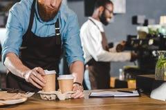 tir cultivé du barman masculin dans le tablier mettant les tasses de café de papier dans le carton et le collègue de sourire util photographie stock