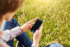 Tir cultivé du garçon adolescent d'étudiant tenant le téléphone intelligent moderne tout en se reposant sur l'herbe verte dans l' Photos stock