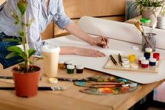 tir cultivé du jeune dessin femelle d'artiste sur la table image stock
