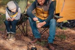 tir cultivé du père et du fils mangeant des haricots de boîte photo libre de droits