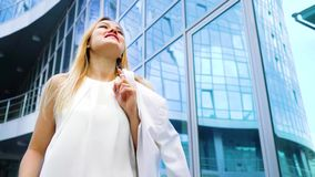 Tir d'angle faible de la femme blonde joyeuse descendant la rue dans le mouvement lent banque de vidéos