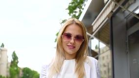 Tir d'angle faible de la jeune femme blonde élégante regardant la caméra et descendant la rue banque de vidéos