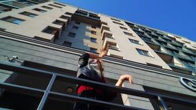 Tir d'angle faible du danseur blond de rue de femme exécutant près du bâtiment moderne clips vidéos