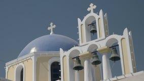 Tir d'angle faible d'un dôme bleu et de quatre cloches d'église au fira, santorini banque de vidéos