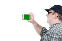 Tir d'homme plus âgé par le téléphone portable avec l'écran vert images stock