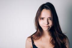 Tir d'intérieur de fille, ayant l'expression douteuse et indécise de visage, poursuivant ses lèvres comme si interdit pour dire n image stock