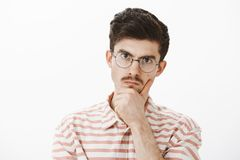 Tir d'intérieur de frère aîné fâché focalisé sérieux avec la moustache en verres à la mode, tenant la main sur le menton et regar Photos libres de droits