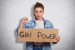 Tir d'intérieur de la position féministe pleine d'assurance énergique au-dessus du fond gris dans le studio avec la puissance de  photo libre de droits