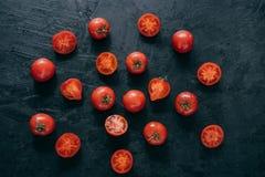 Tir d'isolement des tomates d'héritage de cerise avec les feuilles vertes sur le fond foncé Aliment biologique Moissonnant et man photo libre de droits