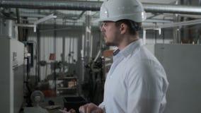 Tir d'ouvrier professionnel utilisant la tablette de prises de casque antichoc, industriel moderne de marche de Thorugh banque de vidéos