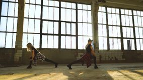 Tir de casserole de deux danseurs féminins professionnels s'étirant dans le vieux bâtiment d'usine banque de vidéos