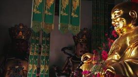 Tir de filtrage lent sur la statue d'or de Bouddha dans le temple chinois banque de vidéos
