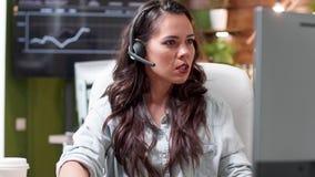 Tir de indication de l'opérateur de service à la clientèle parlant avec un client à l'aide du casque clips vidéos