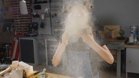Tir de la fille blonde dans le tablier enlevant à l'air comprimé la sciure dans le mouvement lent Enfants en menuiserie HD clips vidéos
