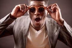 Tir de mâle étonnant d'Afro avec les verres de soleil drôles et de bouche ouverte large dans le costume image stock