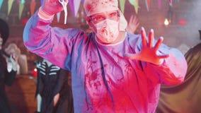 Tir de mouvement lent d'un homme dans le costume fou psychopathe de chirurgien à une partie de Halloween clips vidéos