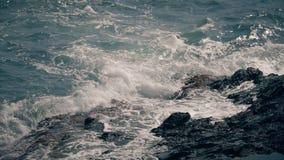 Tir de mouvement lent des vagues de mer éclaboussant sur les roches côtières image stock