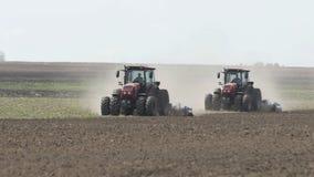 Tir de mouvement lent de deux tracteurs entrant dans la terre oppos?e de direction et de cultivation Tracteur agricole labourant  banque de vidéos