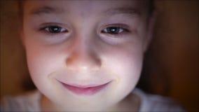 Tir de nuit d'une fin caucasienne mignonne de petite fille du visage d'un enfant regardant une tablette avec une r?flexion de Pig banque de vidéos