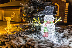 Tir de nuit des cerfs communs et du bonhomme de neige lumineux de Noël Images libres de droits