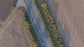 Tir de panorama se levant vers le haut sur la route et les champs Silhouette d'homme se recroquevillant d'affaires banque de vidéos