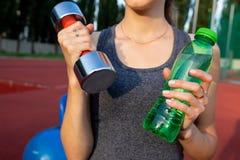 Tir de plan rapproché d'une femme d'ajustement tenant l'haltère et la bouteille d'eau à Image libre de droits