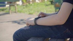 Tir de plan rapproché de montre intelligente avec la courroie noire sur une main d'enfant Poignet intelligent de sport utilisant  banque de vidéos