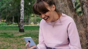 Tir de portrait de la jeune belle femme caucasienne sourie dans la vidéo rose de pull molletonné causant sur son smartphone et banque de vidéos