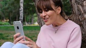 Tir de portrait de la jeune belle fille caucasienne sourie dans la vidéo rose de pull molletonné causant sur son smartphone et banque de vidéos