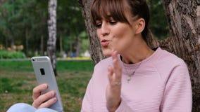 Tir de portrait de la jeune belle fille caucasienne sourie dans la vidéo rose de pull molletonné causant sur son smartphone et clips vidéos