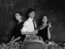 Tir de roman policier dans le studio Homme et deux femmes Agent 007 Un homme dans un chapeau avec un pistolet et deux femmes dans Images libres de droits