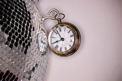 Tir de style bohème d'une grande horloge de montre de poche en métal à côté d'une boule argentée de disco photos libres de droits
