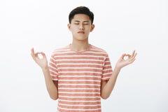 Tir de taille- de l'étudiant masculin asiatique attirant focalisé par calme prenant le contrôle des pensées, se tenant dans la po images libres de droits