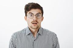 Tir de taille- de type barbu drôle étonné choqué avec la moustache dans l'eyewear transparent rond, mâchoire de chute, dire photo libre de droits