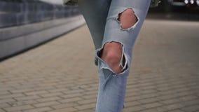 Tir des jambes de femme dans des jeans déchirés marchant sur la route de tuile milieu urbain banque de vidéos