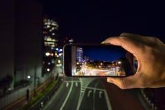 Tir des lumières de ville avec un périphérique mobile Photographie stock libre de droits