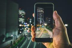 Tir des lumières de ville avec un périphérique mobile Photo libre de droits